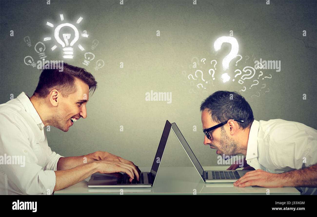 Side profile two men using laptop computer one educated has bright ideas the other ignorant has many questions. - Stock Image
