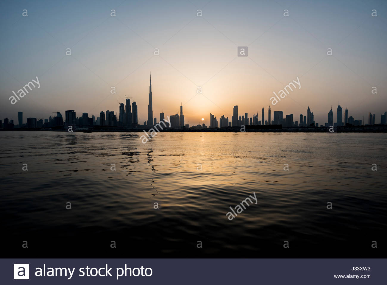 Silhouette of Dubai during a nice sunset on the city, view from the water canal, Ras Al Khor side. United Arab Emirates - Stock Image