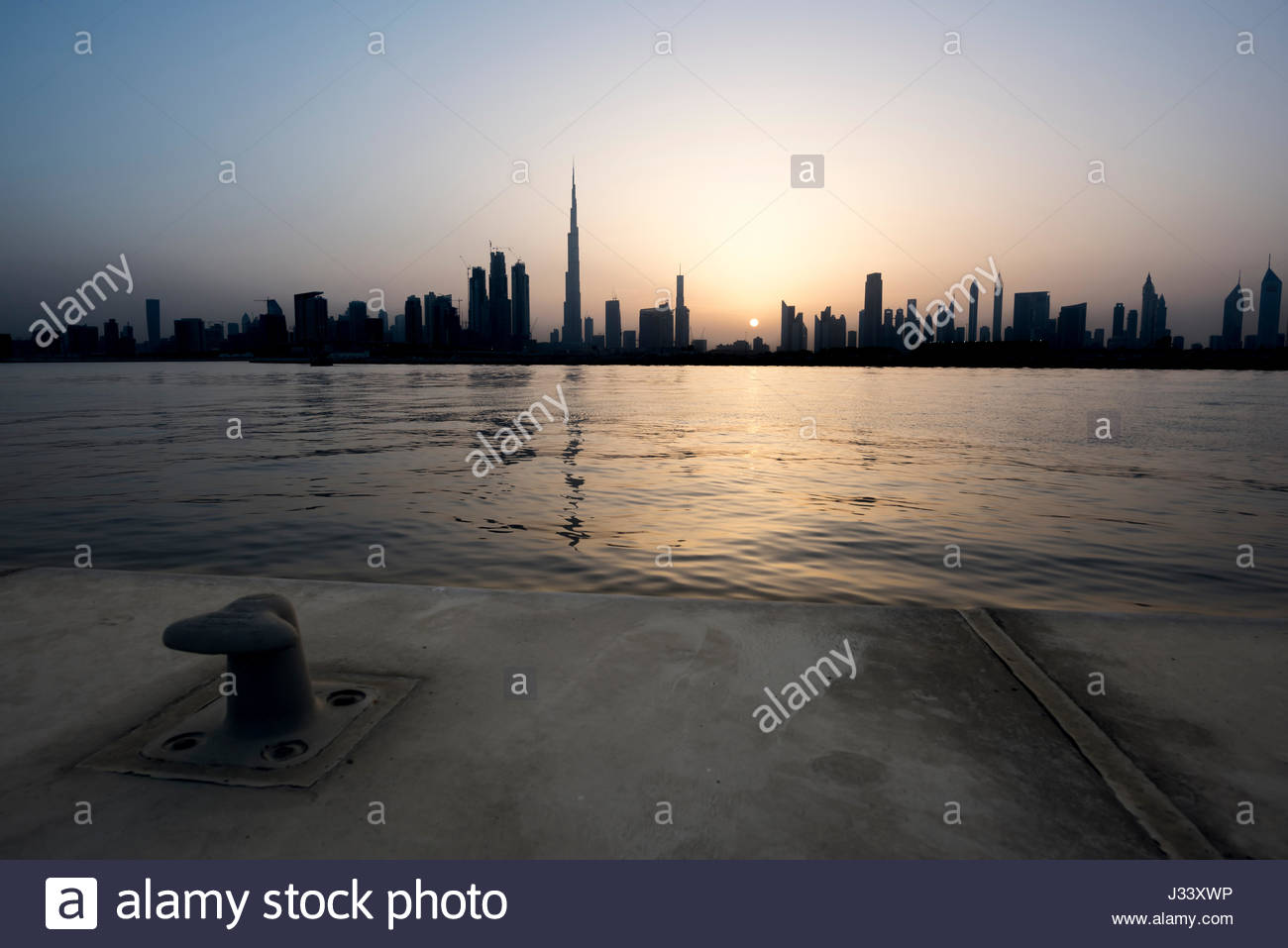 Silhouette of Dubai during a nice sunset on the city, view from the water canal with anchor hook in foreground, - Stock Image