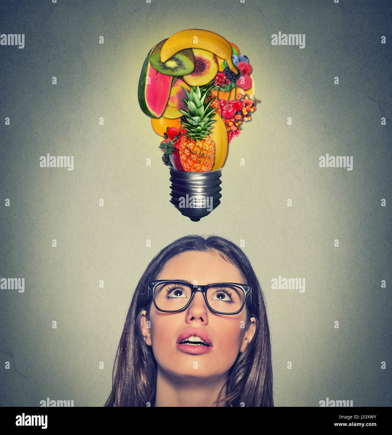 Eating healthy idea and diet tips concept. Closeup portrait headshot woman looking up light bulb made of fruits - Stock Image