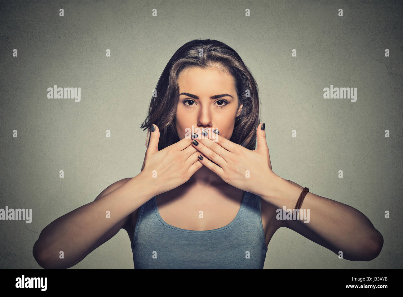 Closeup portrait of young woman covering with hands her mouth isolated on gray wall background Stock Photo
