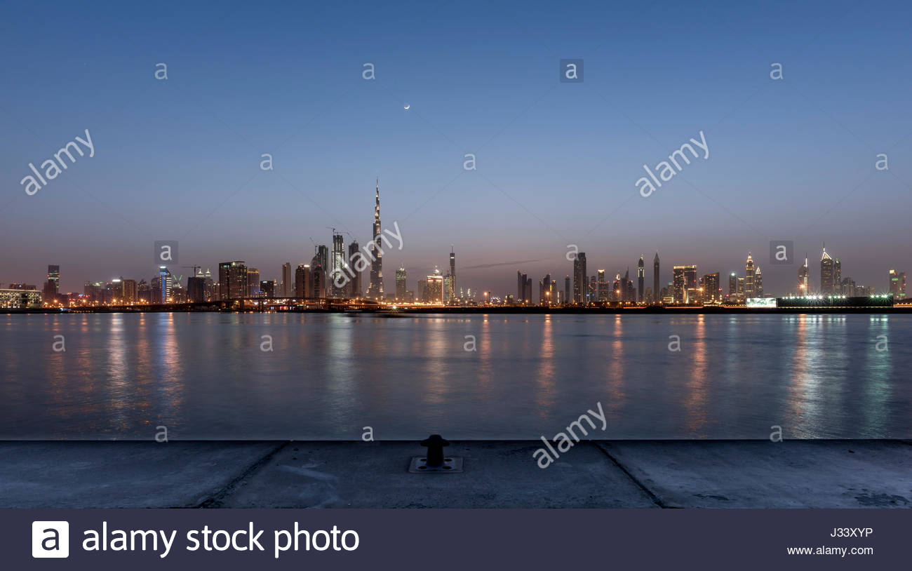 Panoramic view of Dubai at sunset with the moon above the city, United Arab Emirates - Stock Image