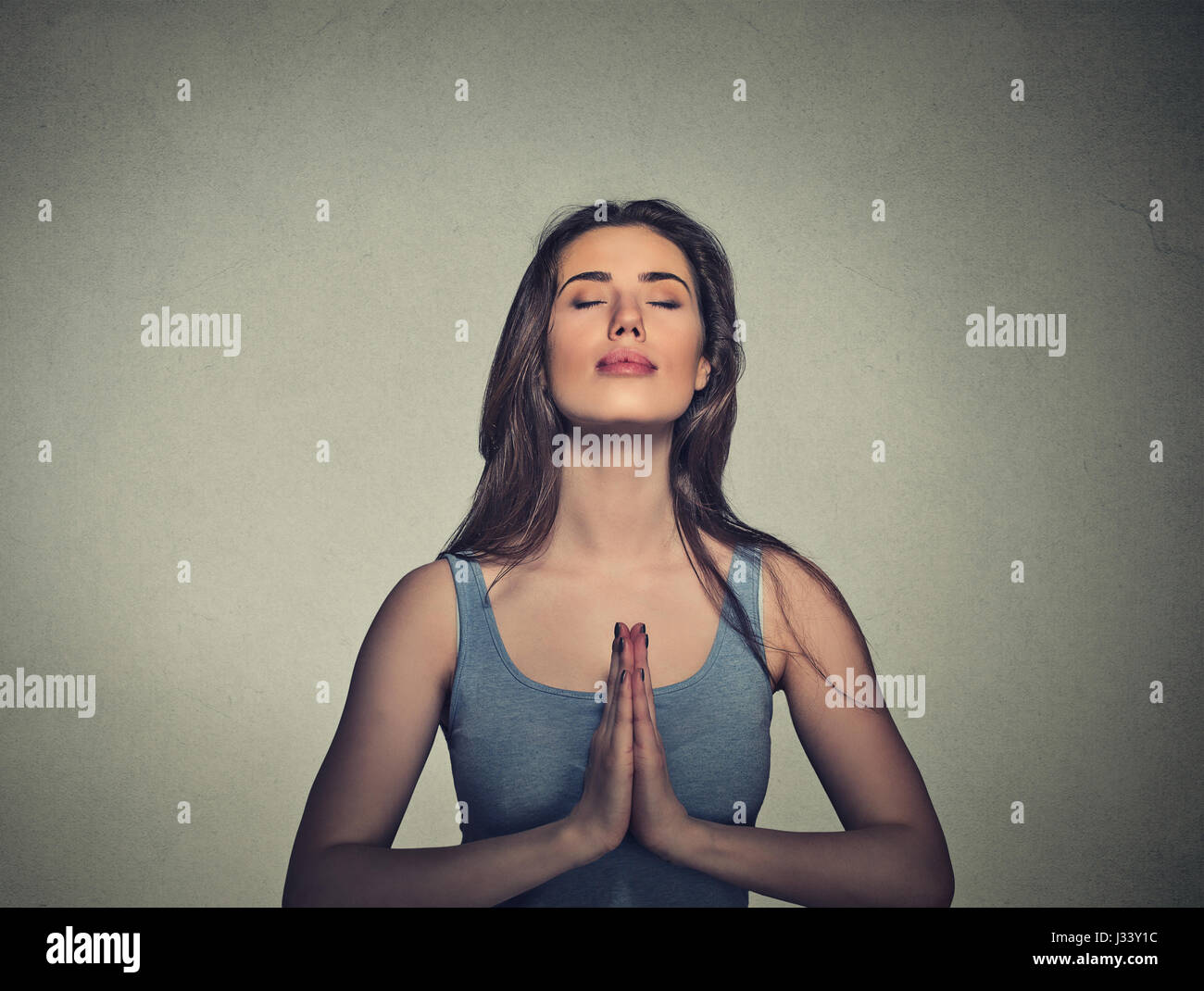 Portrait beautiful woman meditating with eyes closed isolated on gray wall background Stock Photo