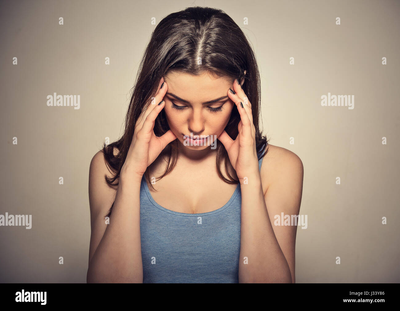 Closeup portrait sad young beautiful woman with worried stressed face expression looking down - Stock Image