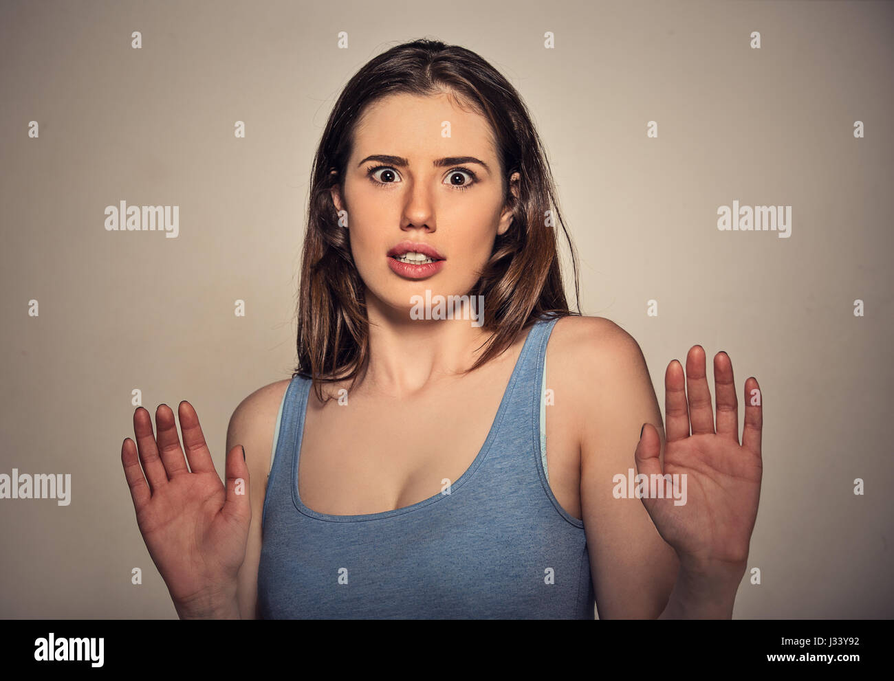 Concerned scared woman dodging something arms raised trying to avoid unpleasant situation isolated on gray wall - Stock Image