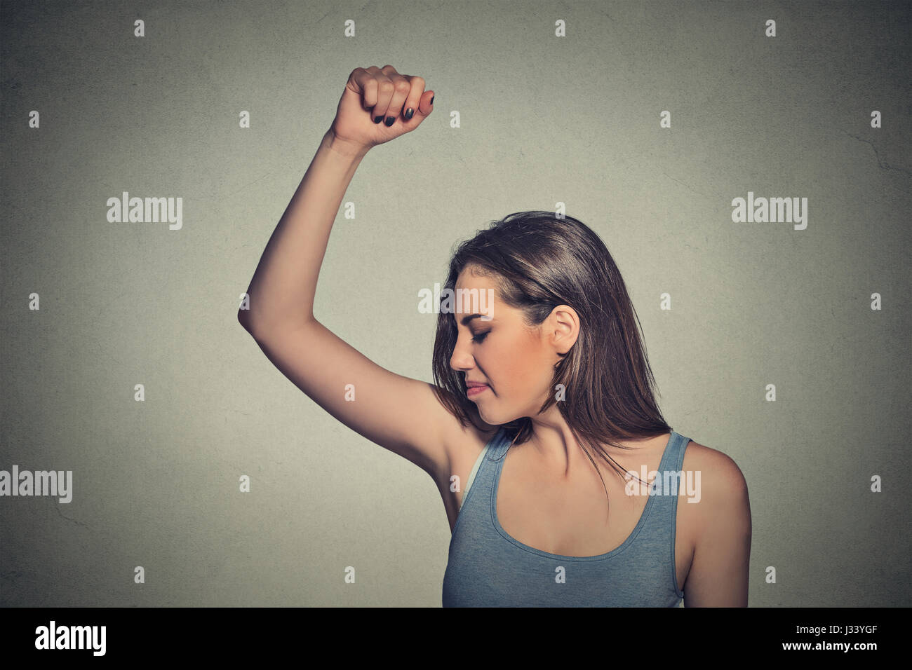 Closeup portrait young woman, smelling, sniffing her wet armpit, something stinks, very bad foul odor situation - Stock Image