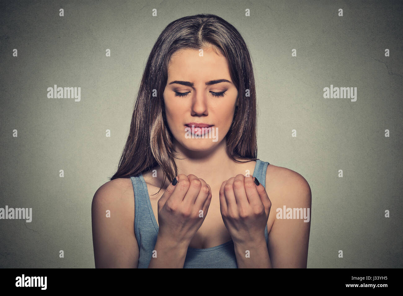 Worried woman looking at hands fingers nails obsessing about cleanliness isolated on grey background. Negative human - Stock Image