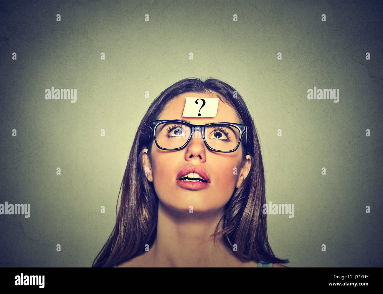 Thoughtful woman looking up - Stock Image