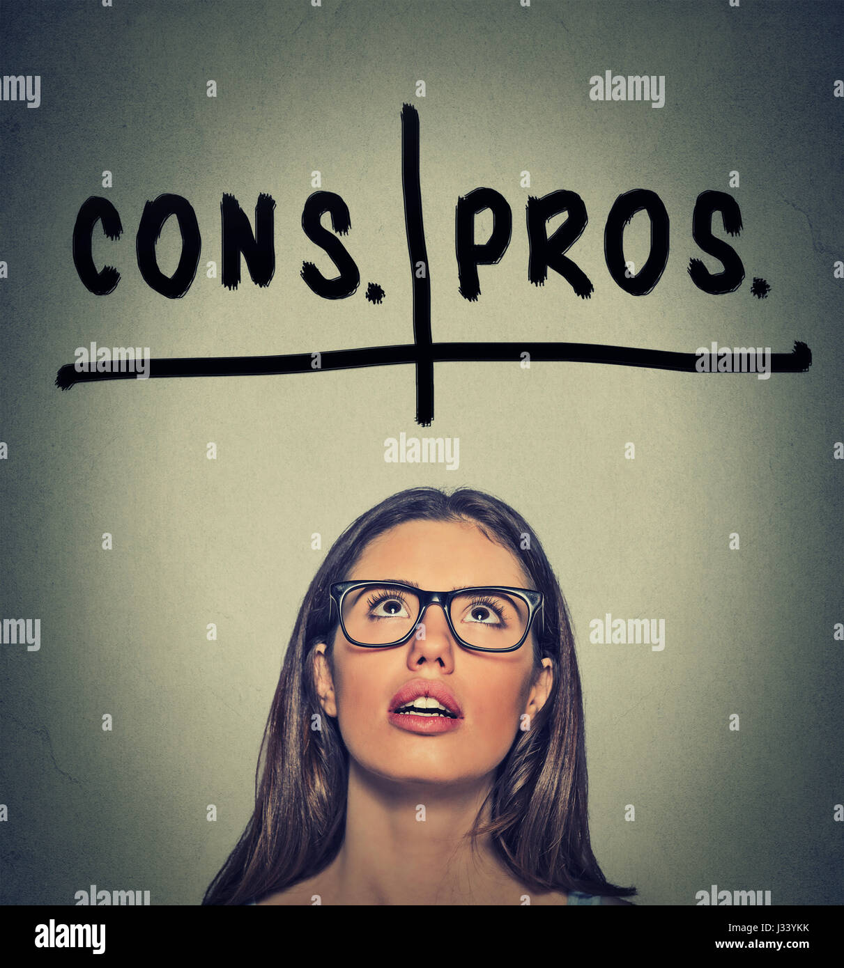 pros and cons, for and against argument concept. Young business woman with glasses looking up deciding isolated - Stock Image