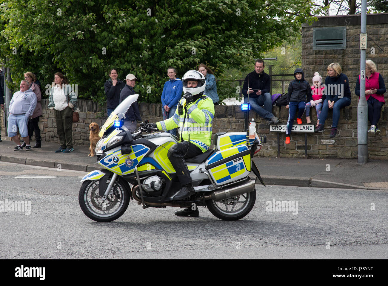 Police motorbike and rider controlling crowd - Stock Image