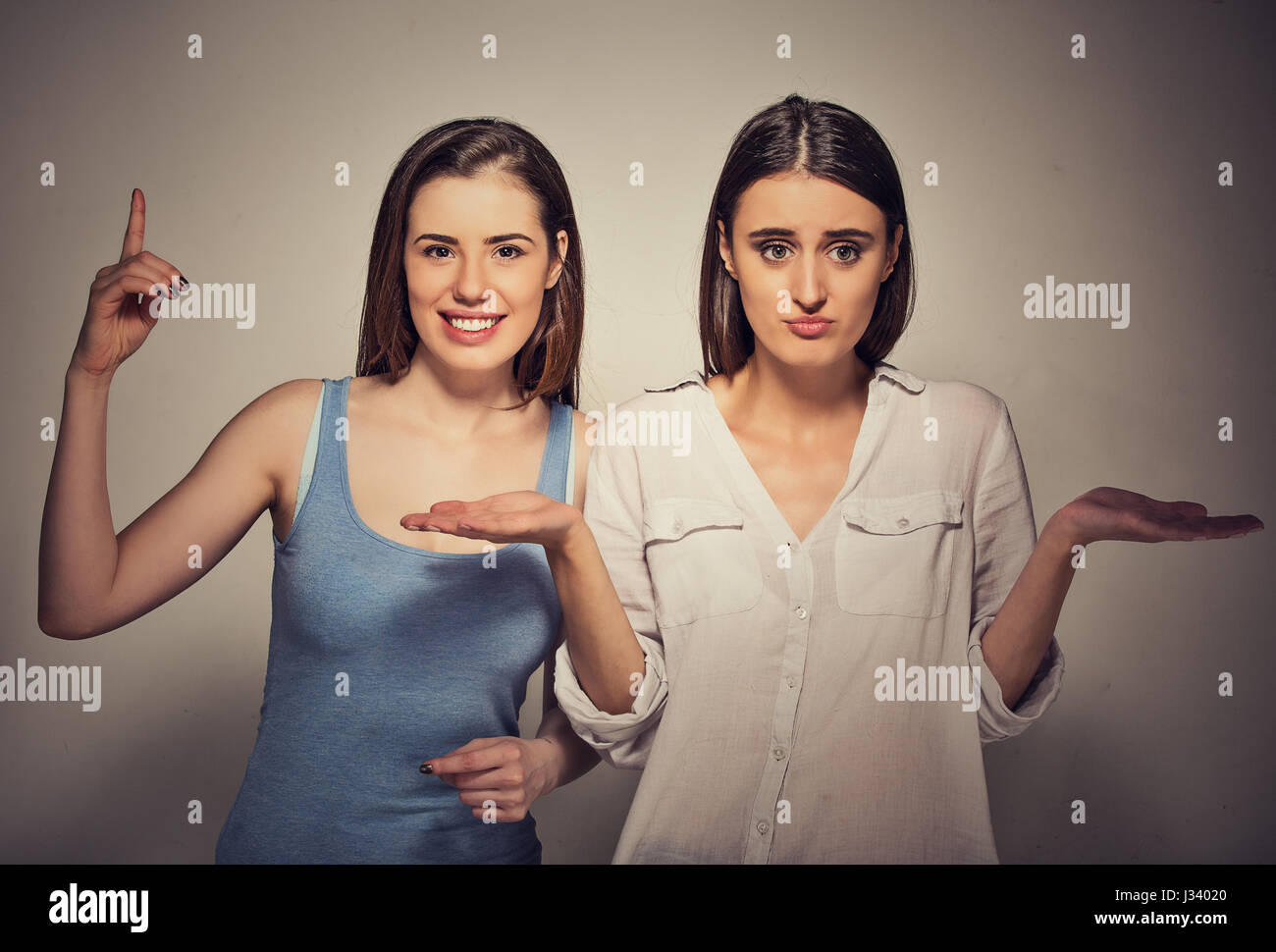 Closeup portrait excited, optimistic woman having solution, and bored, annoyed clueless girl isolated on gray background. - Stock Image