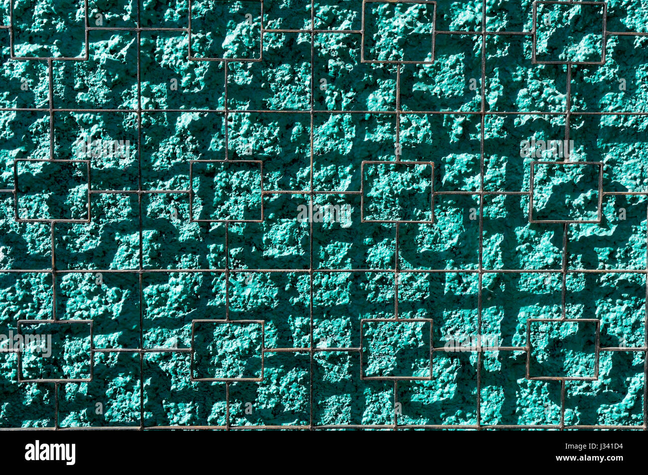 Wire grid casting square shadows on a bright green stucco wall abstract background - Stock Image