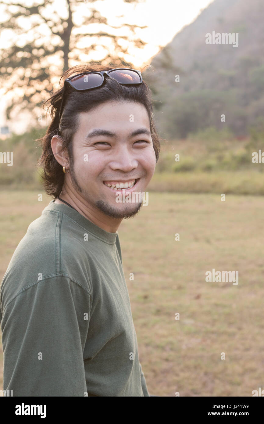 asian younger man toothy smiling face happiness emotion standing outdoor - Stock Image