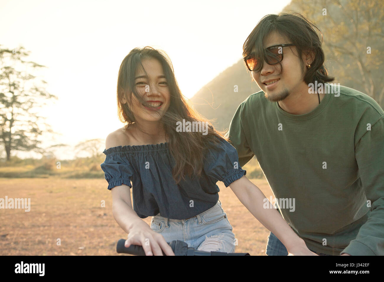 couples of younger asian man and woman practice to riding bicycle in natural field relaxing emotion - Stock Image