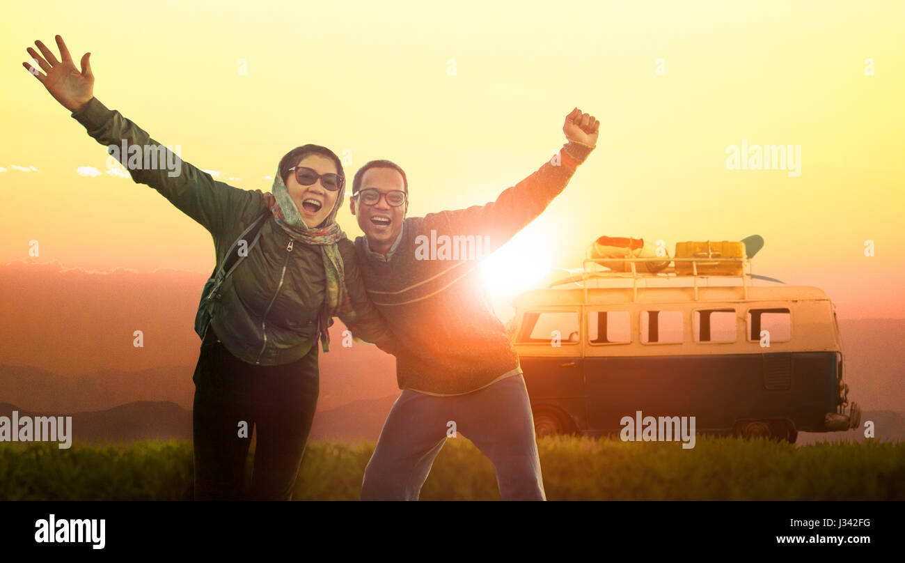 younger man and woman happiness emotion traveling to destination against beautiful sun set sky - Stock Image