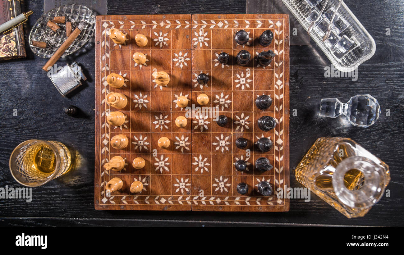 Top down view of a game of chess with a glass of whiskey and a cigar - Stock Image