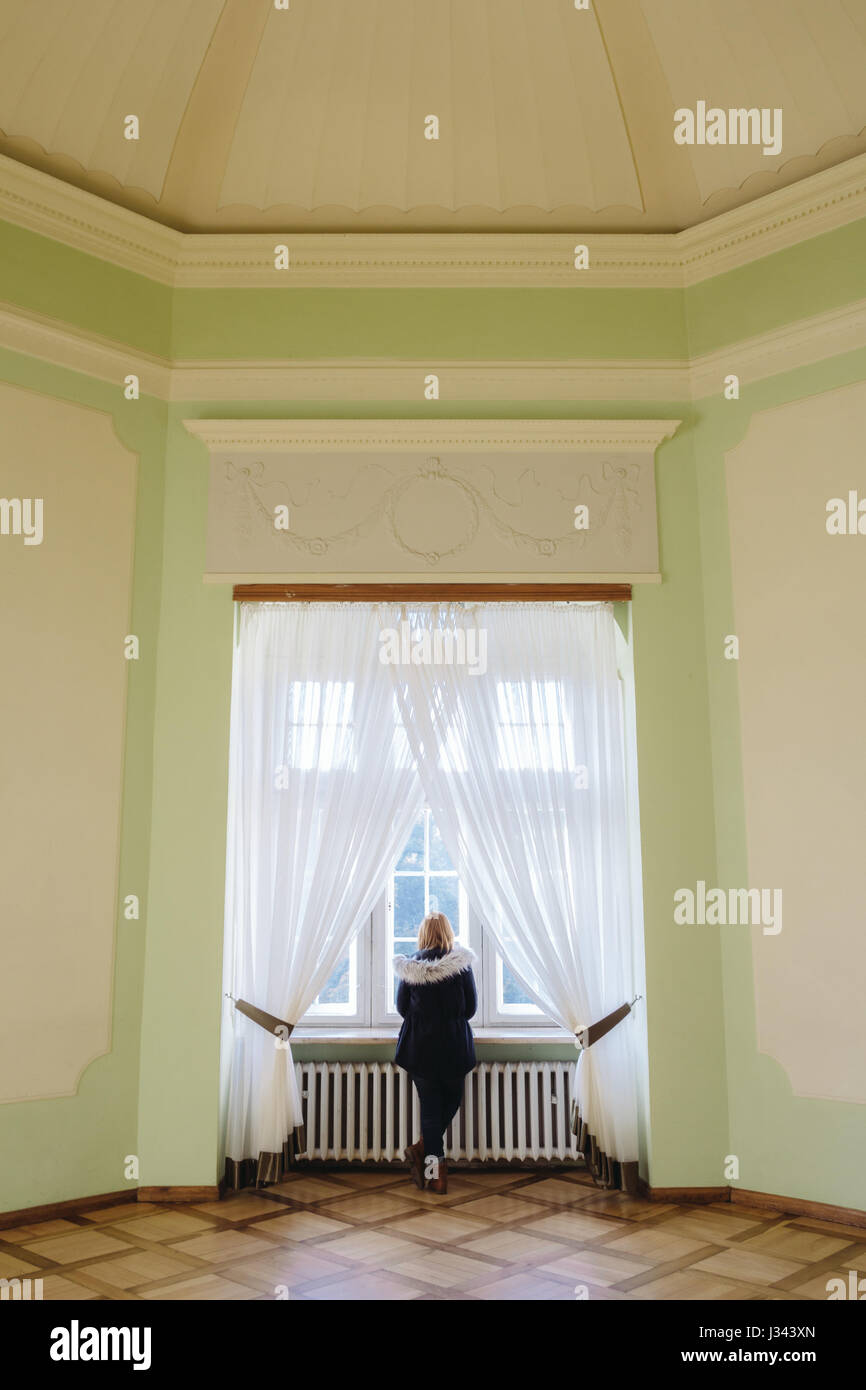 A woman looks out of a window in a large ornate european palace. - Stock Image