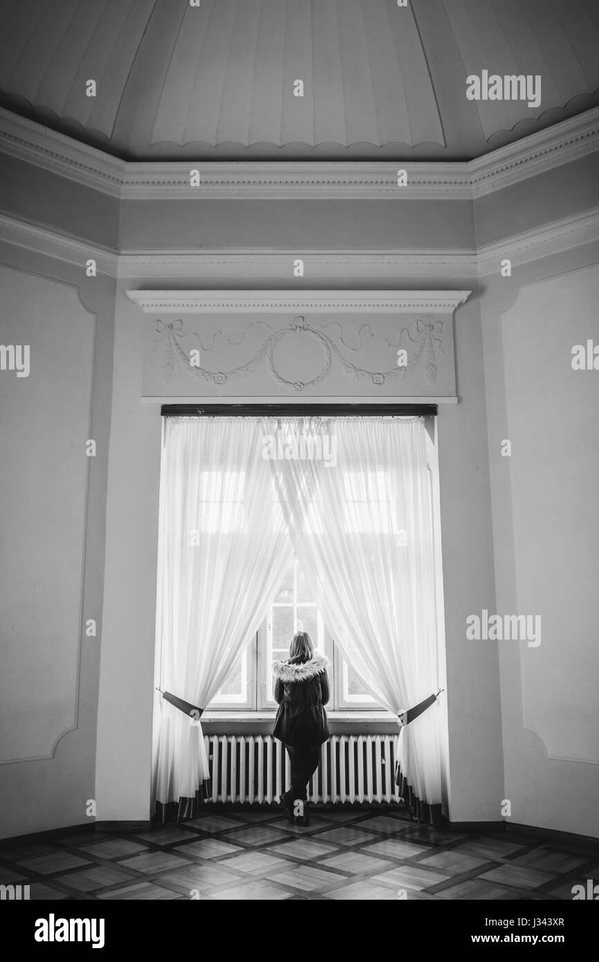 A woman looks out of a window in a large ornate european palace in black and white. - Stock Image
