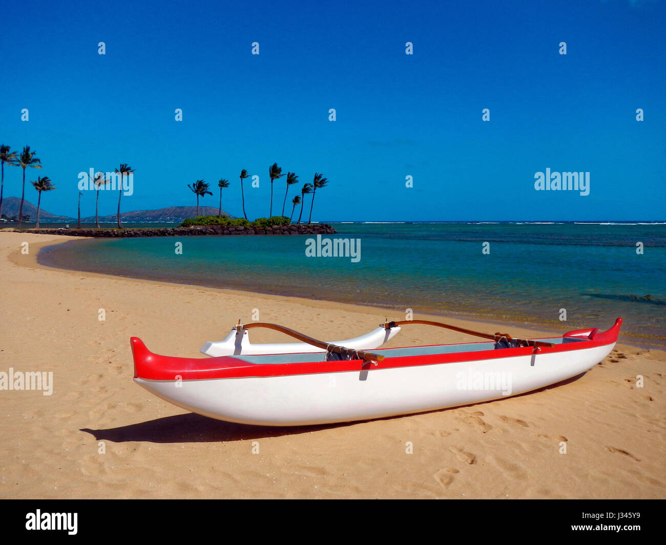 Red and white outrigger canoe on a sandy beach and blue sky in Hawaii - Stock Image