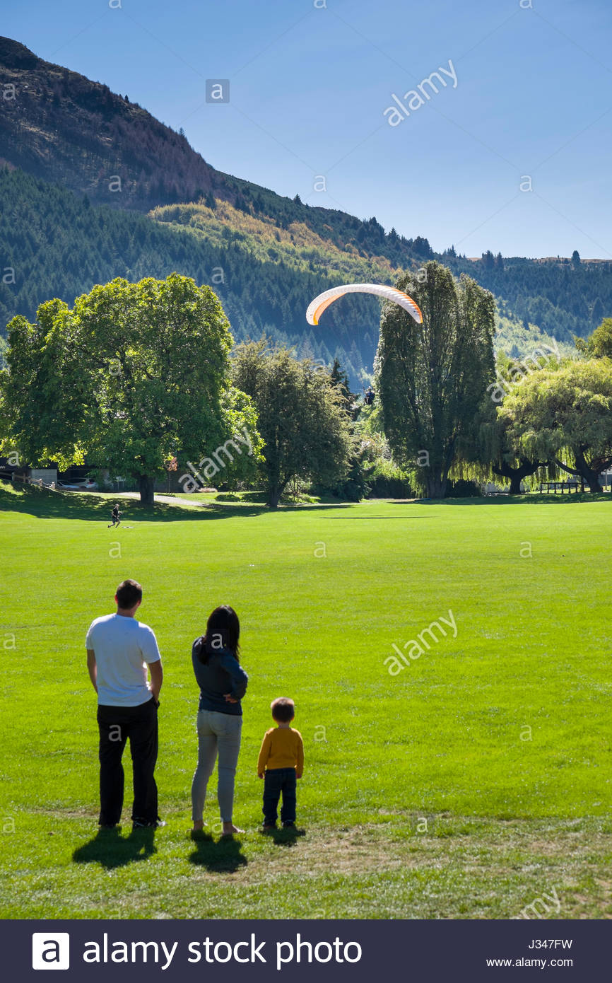 Man, woman and child watching a paraglider landing on the field at Queenstown Recreation Ground, Queenstown, Otago, Stock Photo