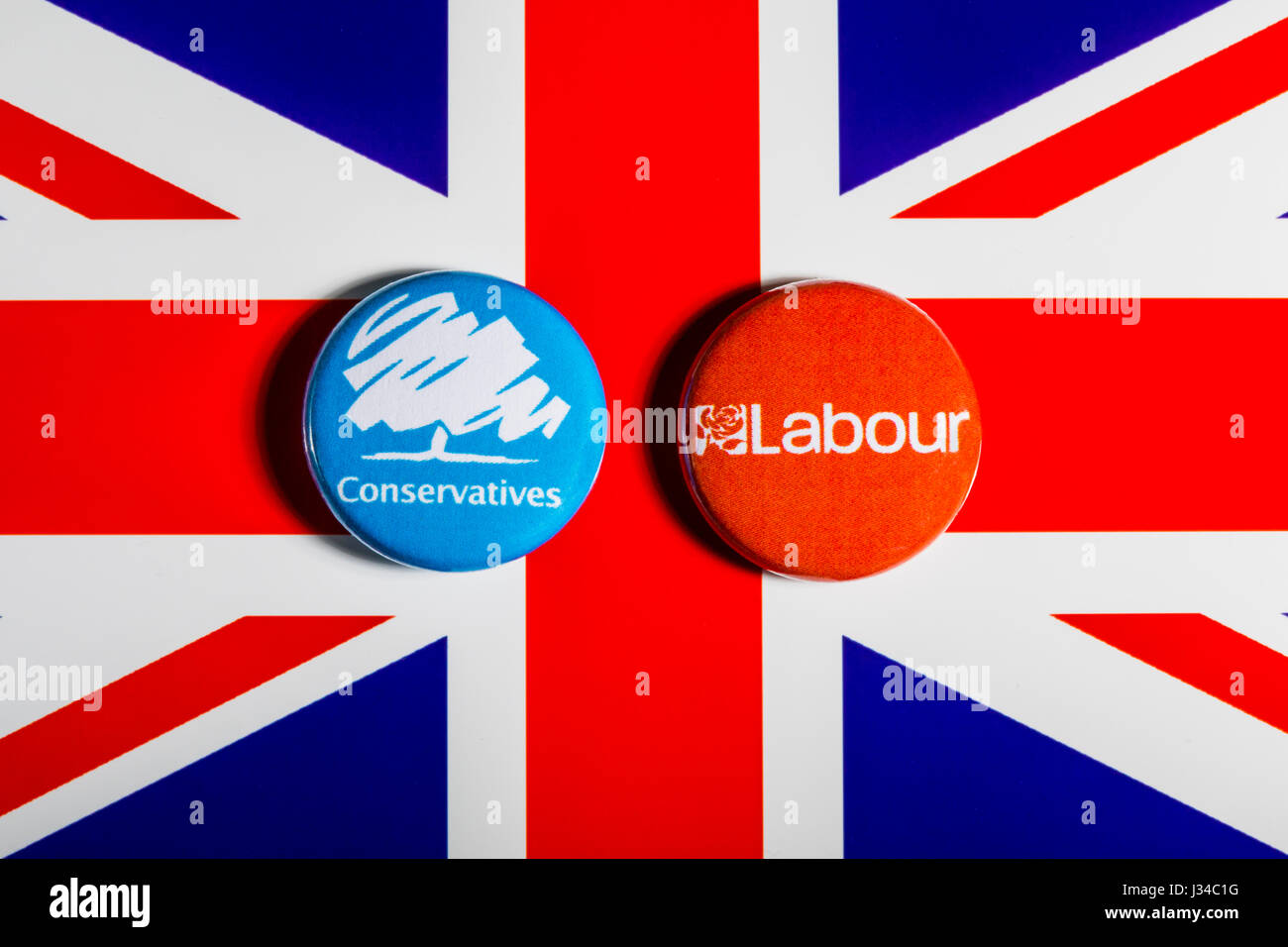 LONDON, UK - MAY 2ND 2017: Conservative and Labour Party pin badges over the UK flag, symbolizing the political - Stock Image