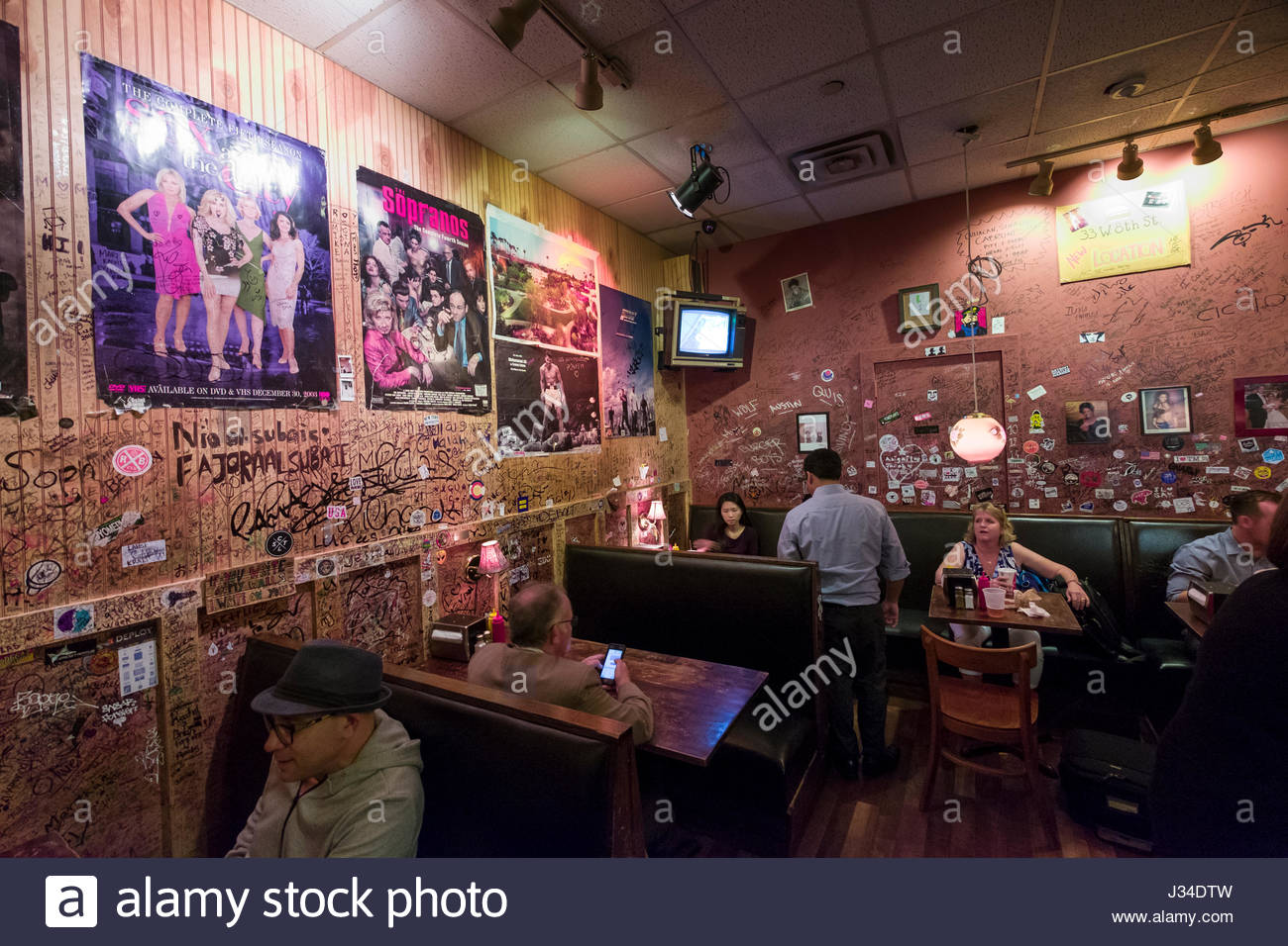 People sitting in booths and at counter eating lunch in the burger joint W 56th St., New York, NY, USA - Stock Image