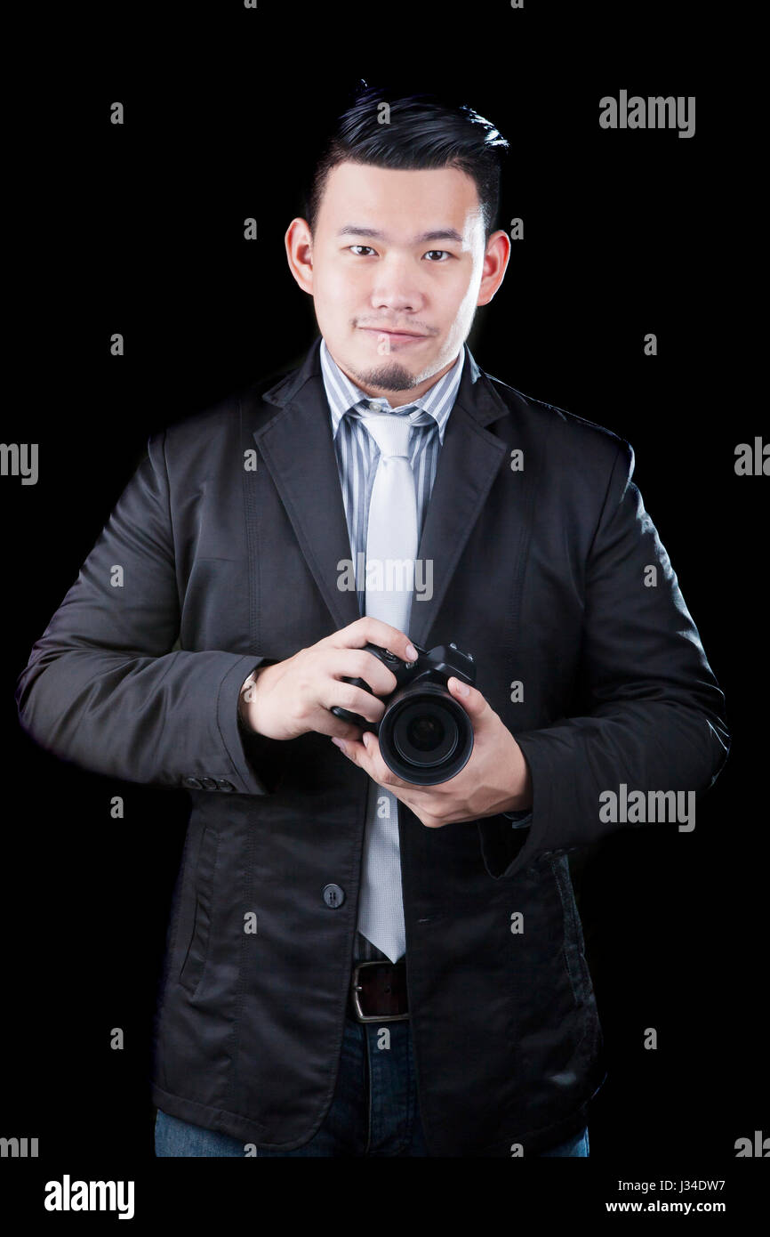 young asian man holding dslr camera take a photography by low key low light white dark background technical use for people activities and human occup  sc 1 st  Alamy & young asian man holding dslr camera take a photography by low key ...
