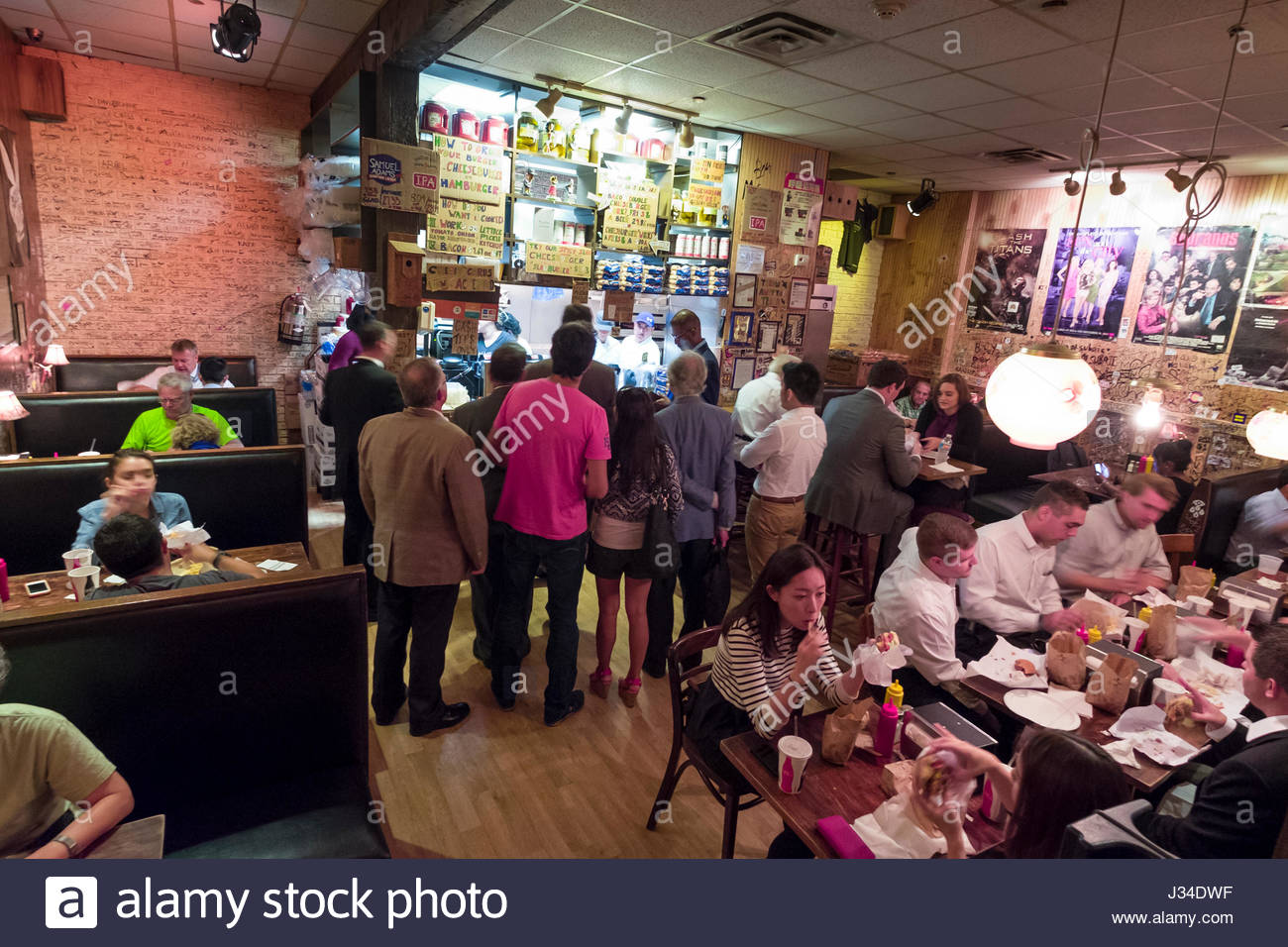 People standing in line to order lunch at the burger joint, W 56th St., New York, NY, USA - Stock Image