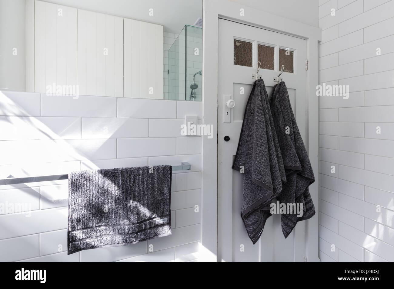 Luxury towels on door hooks in modern white bathroom with brick ...