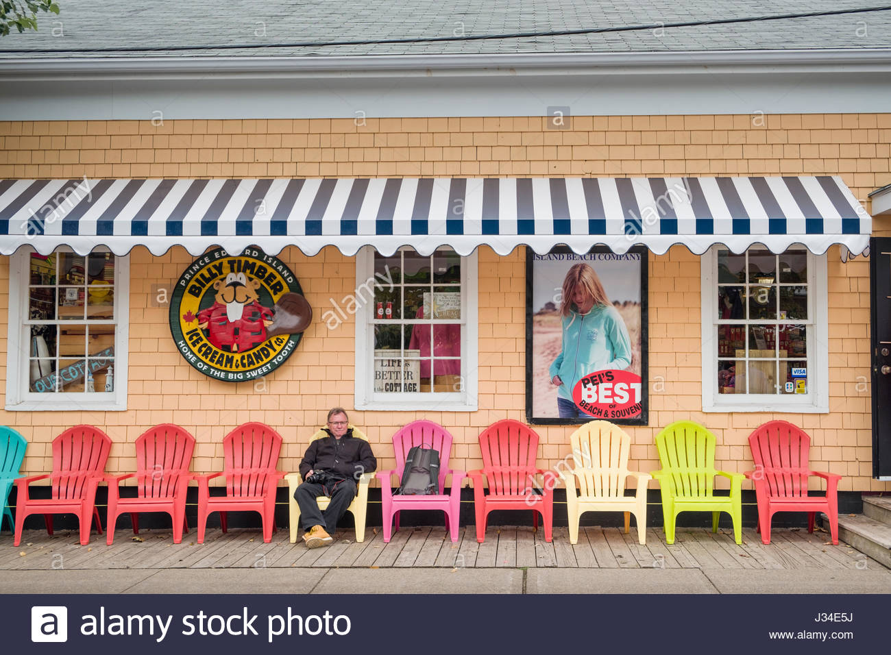 Man Sitting On Plastic Chair Among Row Of Colorful Plastic Chairs,  Charlottetown, Prince Edward Island, Canada