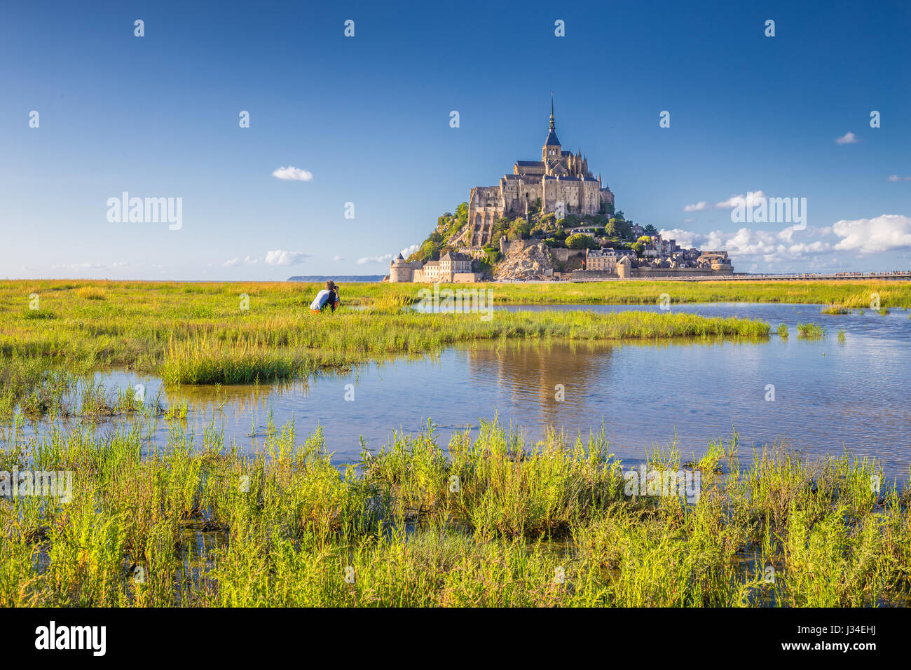 Classic view of famous historic Le Mont Saint-Michel tidal island on a sunny day with blue sky and clouds in summer, - Stock Image