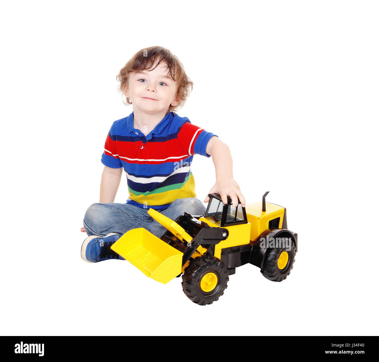 A closeup image of a three year old boy sitting on the floor playing with his toy truck, isolated for white background. - Stock Image