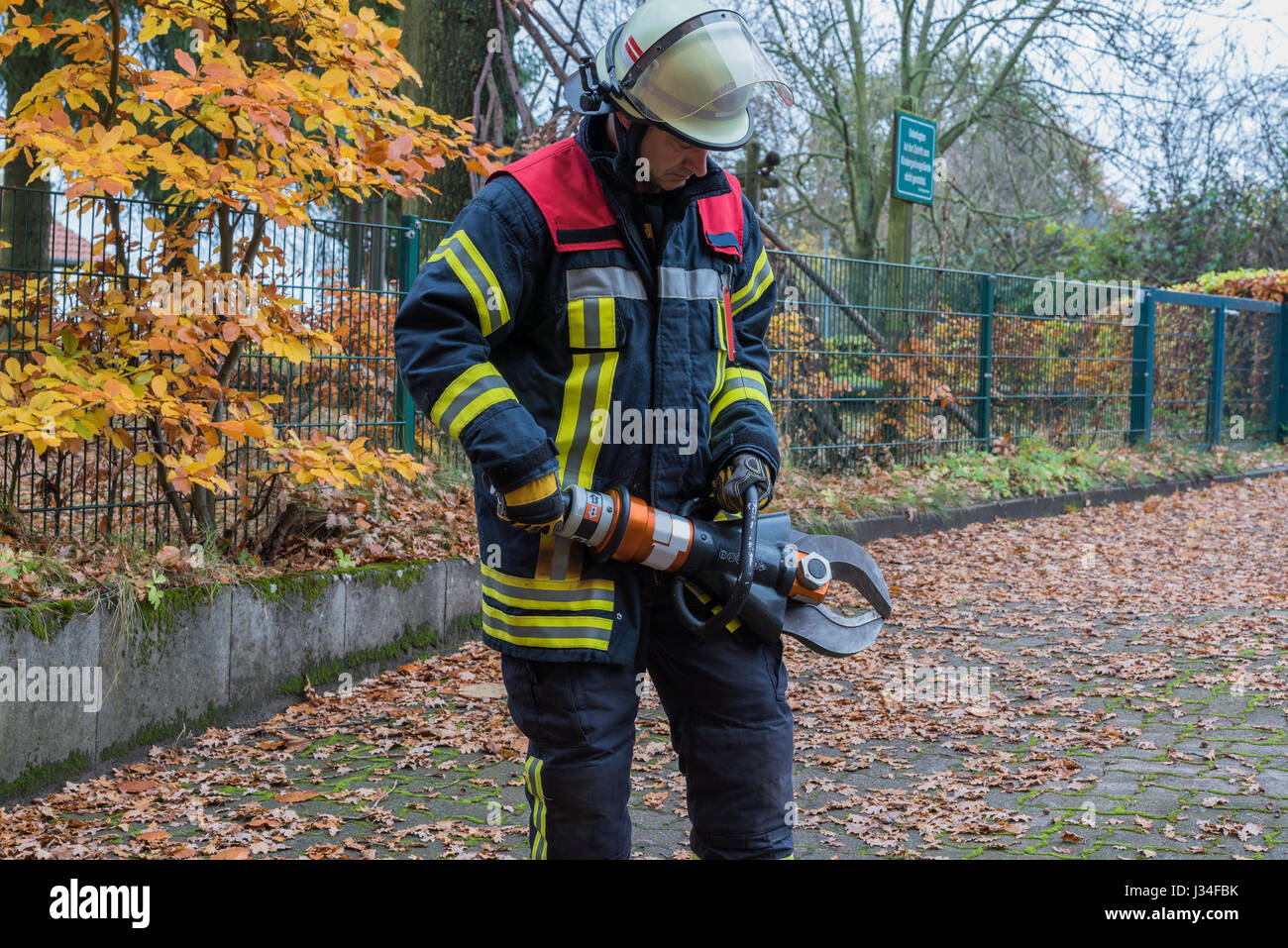 German firefighter in action with pliers for emergency use - Stock Image