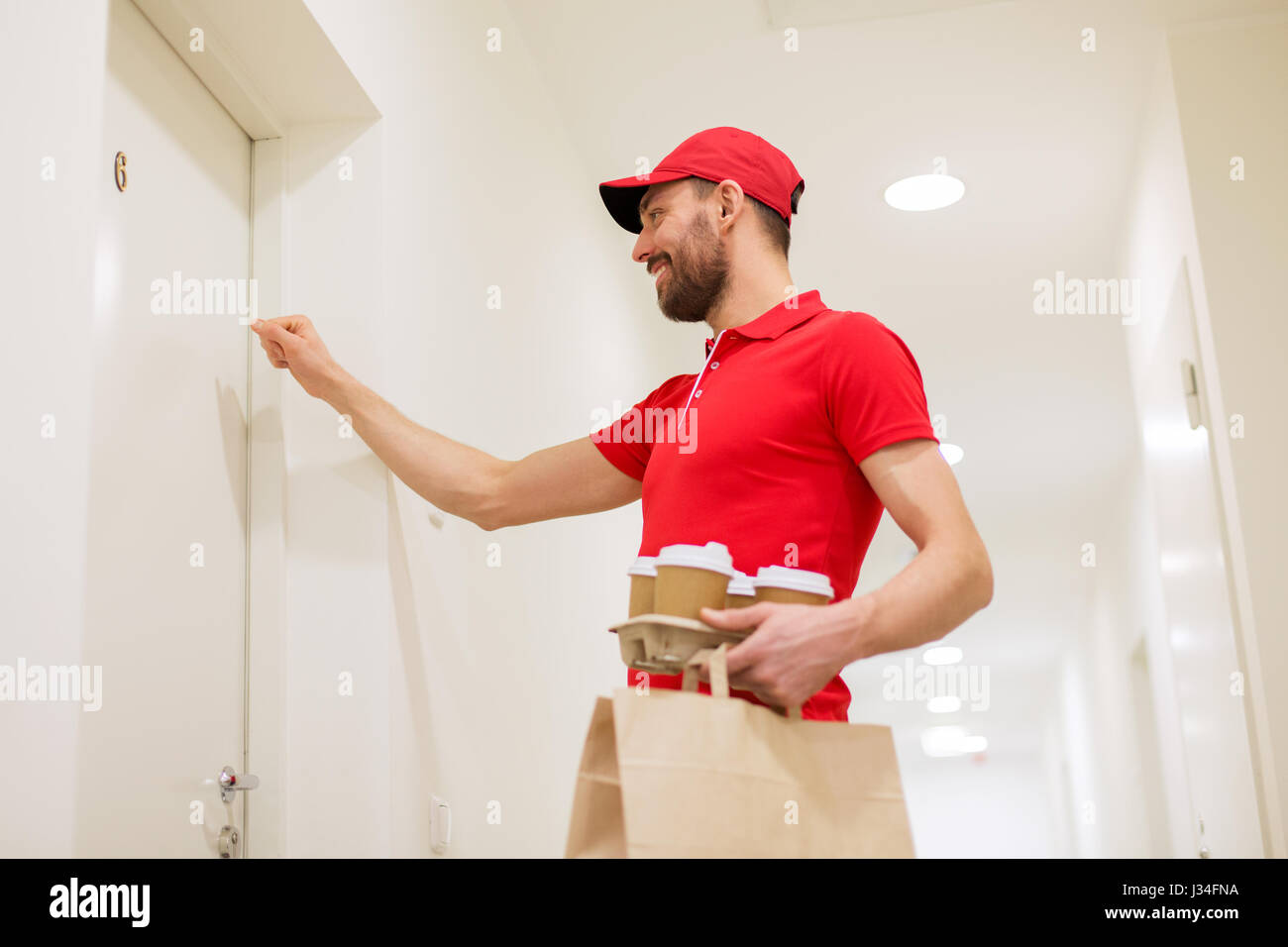 delivery man with coffee and food knocking on door - Stock Image