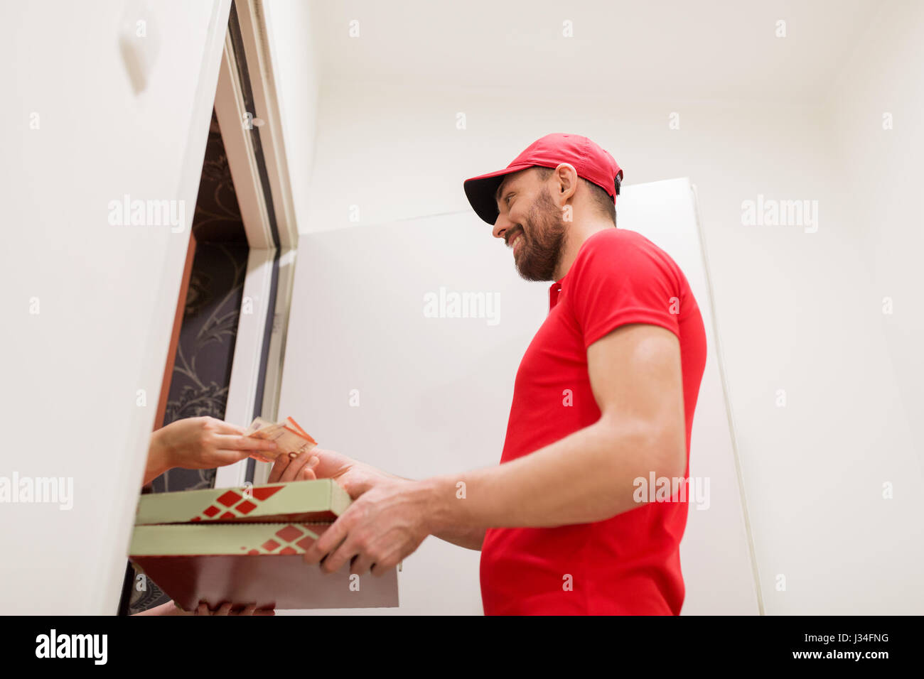 man delivering pizza to customer and taking money - Stock Image