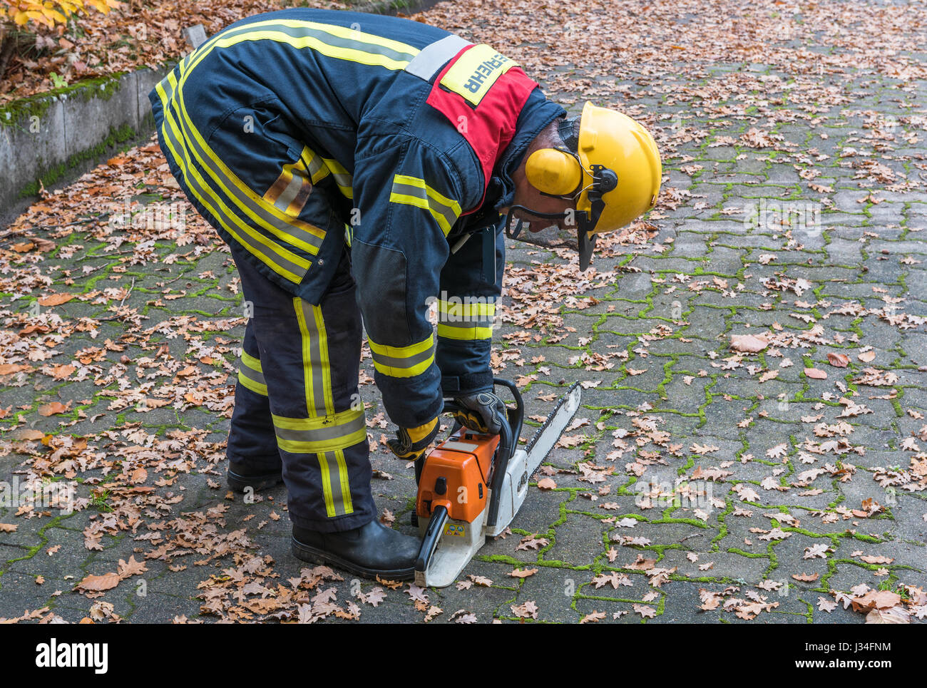 German Fireman in action outdoors with chainsaw - Stock Image
