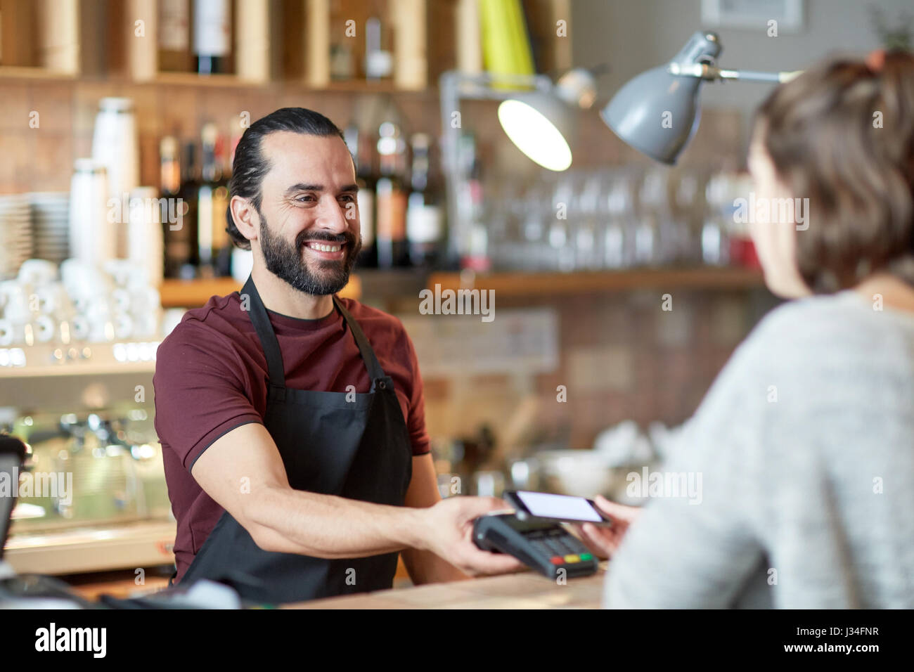 barman and woman with card reader and smartphone Stock Photo