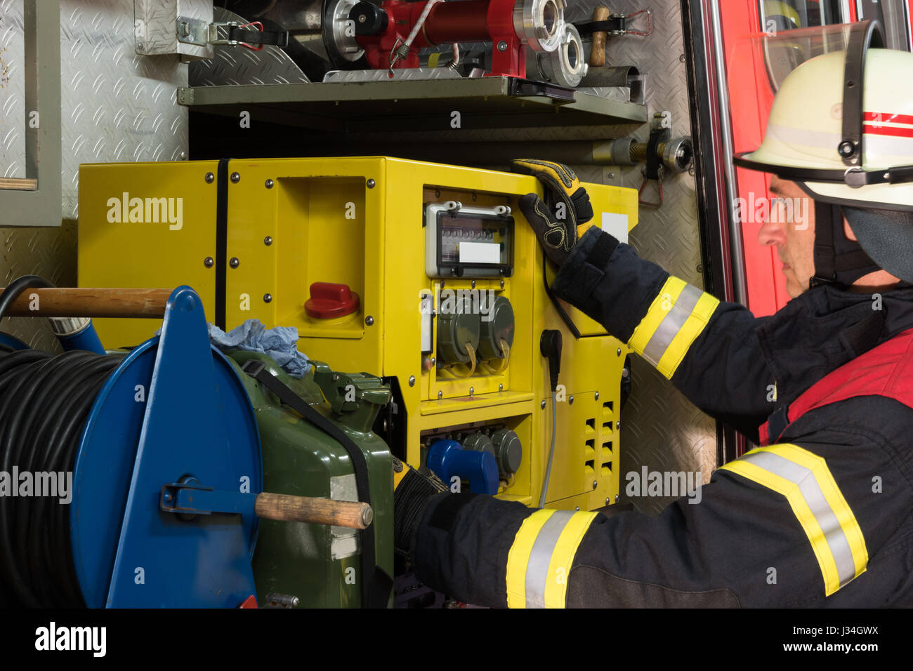 German firefighter on the fire truck and operated power generator - Stock Image