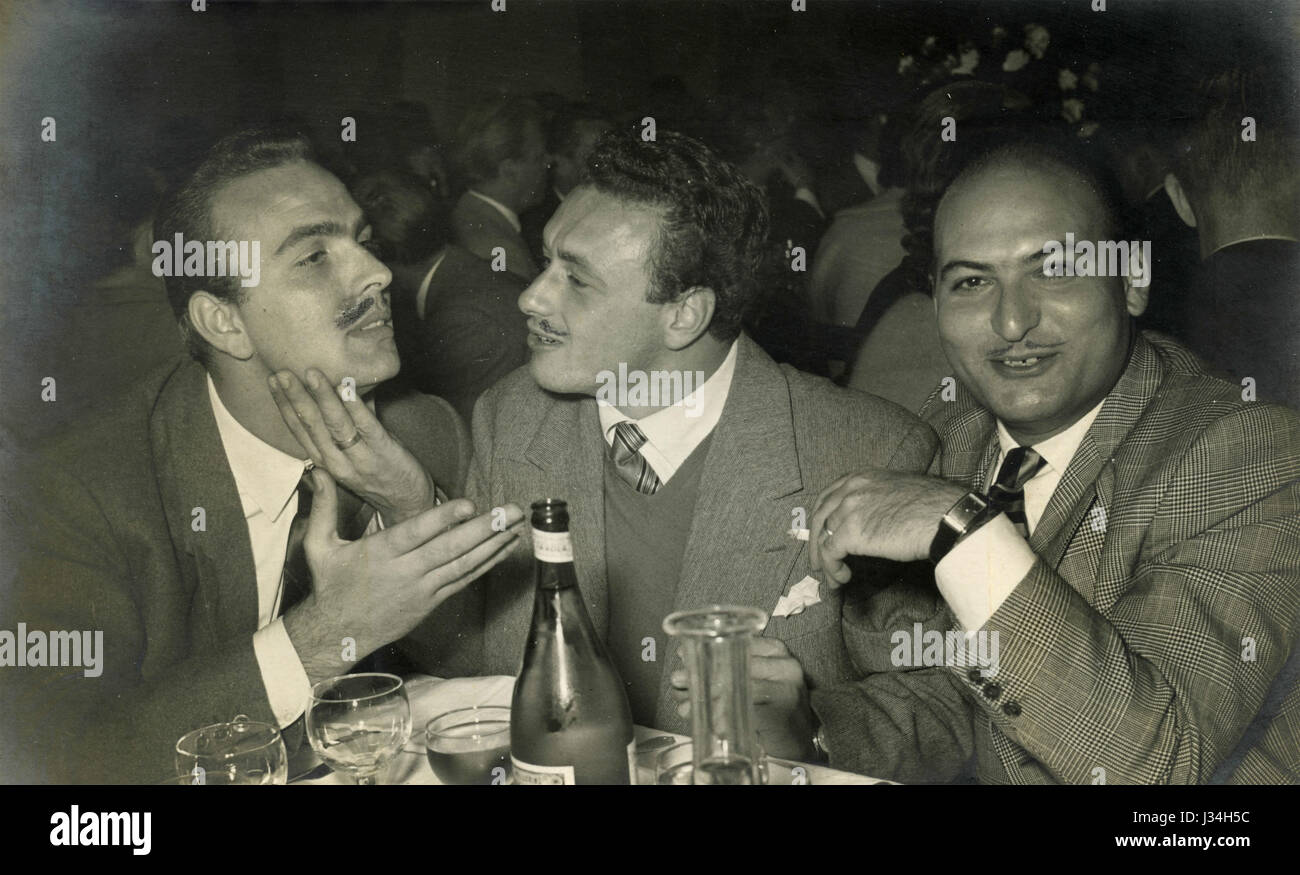 Three men enjoying at the restaurant, Italy 1956 - Stock Image
