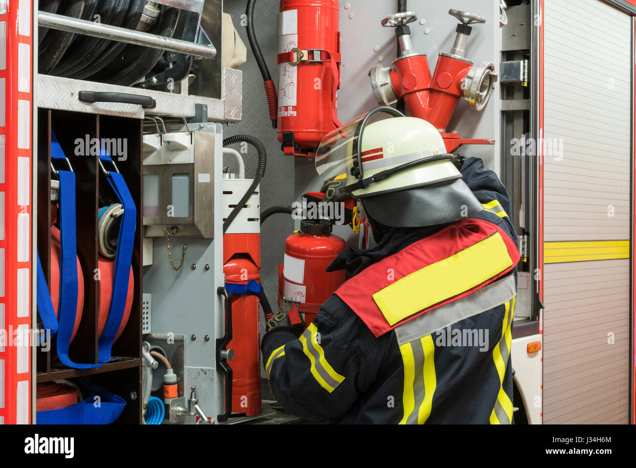 German firefighter with fire extinguisher on the fire truck - Stock Image