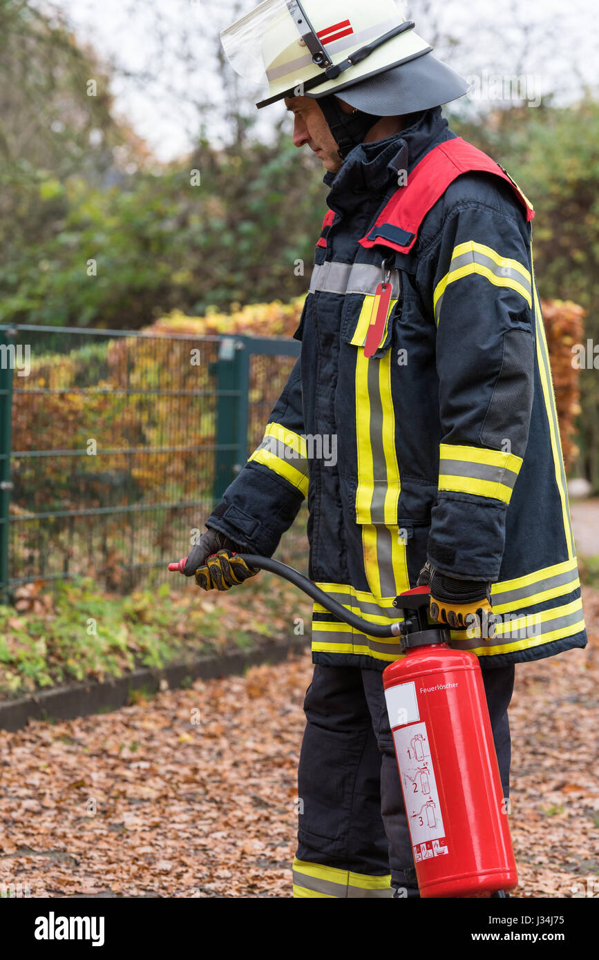 German firefighter in a action with a fire extinguisher - Stock Image
