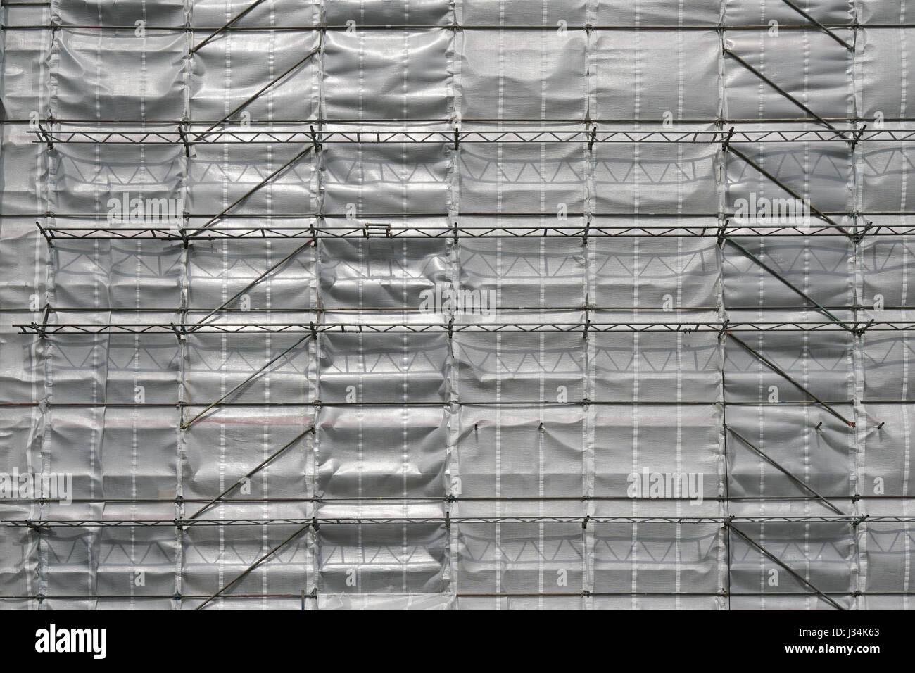 scaffolding and tarpaulin - Stock Image