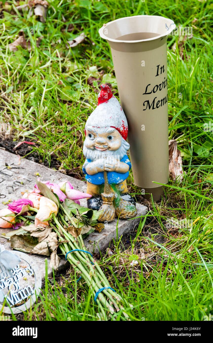 Garden gnome on a grave as a memorial.. Stock Photo