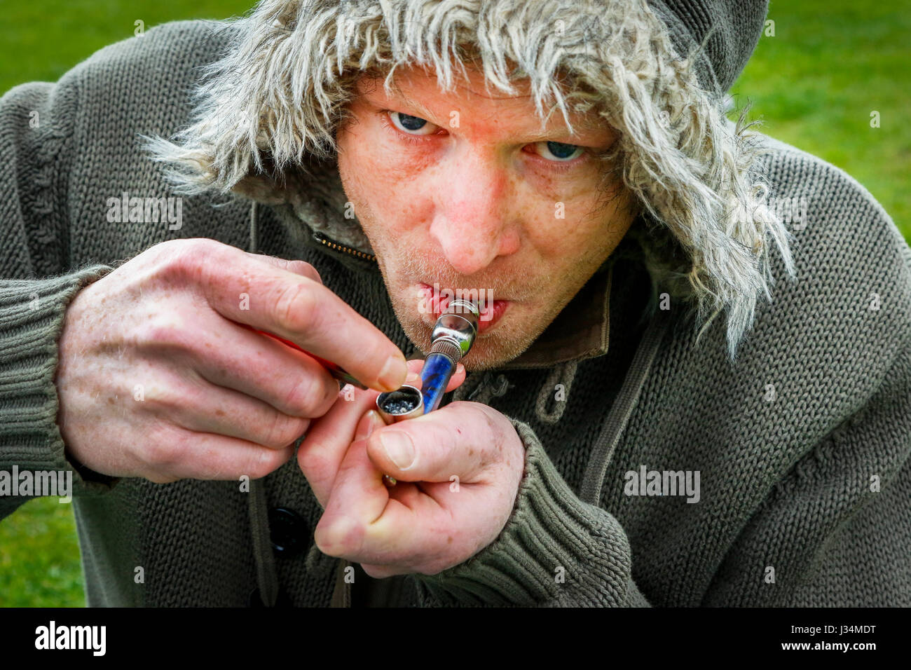 Drug user lighting up his cannabis pipe, Glasgow, Scotland, UK - Stock Image