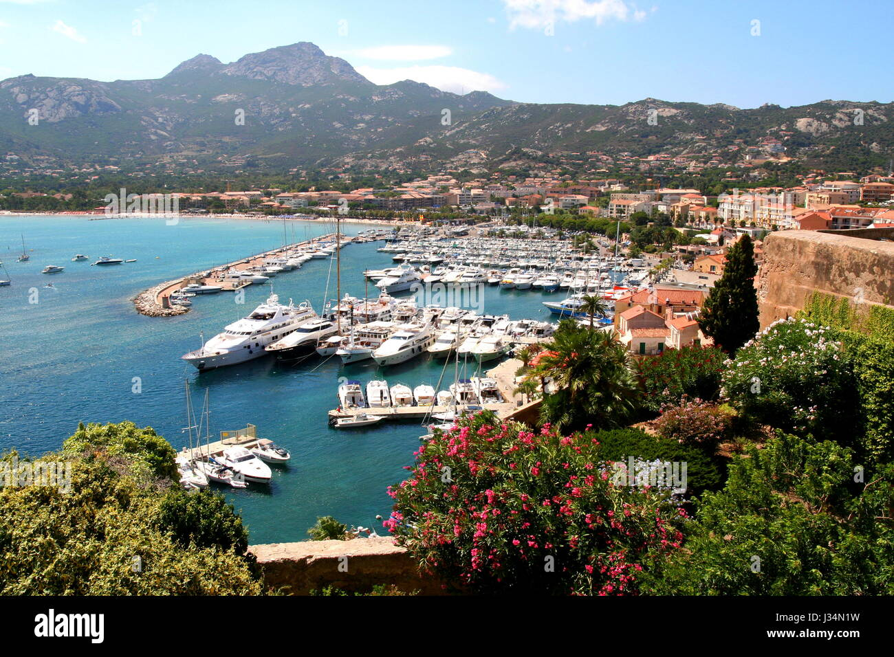View of Calvi marina on Corsica, from the citadel. The rugged highlands of the islands interior are visible in the - Stock Image