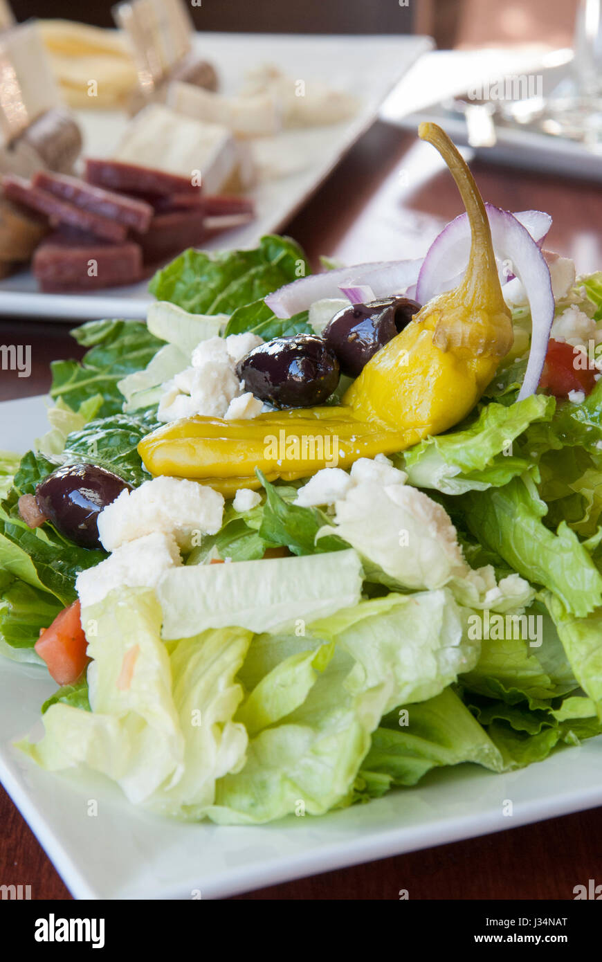 A fresh Greek salad with kalamata olives, feta cheese, and peperoncino makes a lite and healthy lunch, accompanied - Stock Image