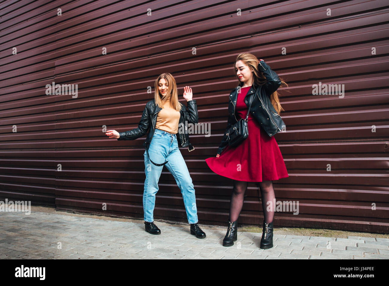 Two Women Talking in the City.Outdoor lifestyle portrait of two best friends hipster girls wearing stylish Leather - Stock Image