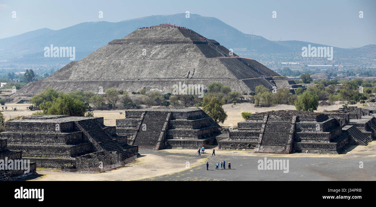 Teotihuacan, Mexico - 21 April 2017: Tourists atop and climbing the Pyramid of the Sun with other tourist in plaza - Stock Image
