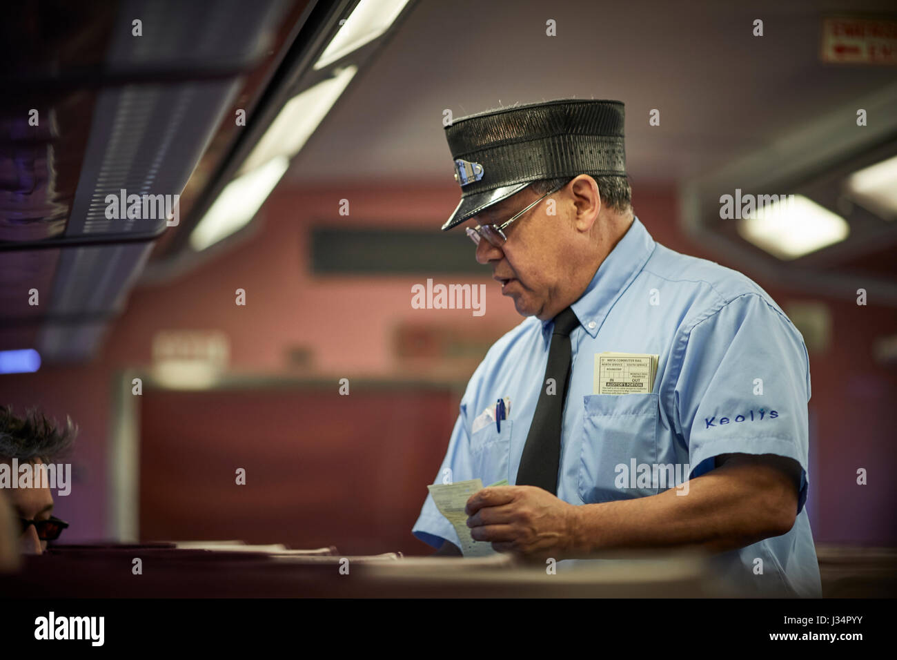 Massachusetts Bay Transportation Authority guard inspecting tickets on a train to Boston, Massachusetts, United - Stock Image