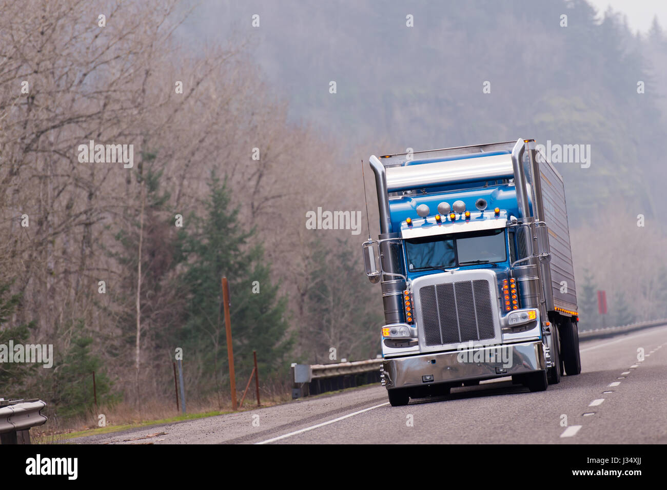 big classic rig semi truck with reefer semi trailer in blue driving on hiway with forest
